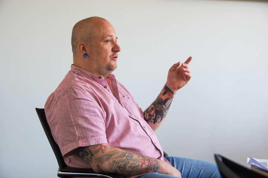 Ein Mann im rosa Hemd spricht und nutzt dabei seine Hände. Er trägt Glatz und 3-Tage-Bart. Seine Arme sind tätowiert.