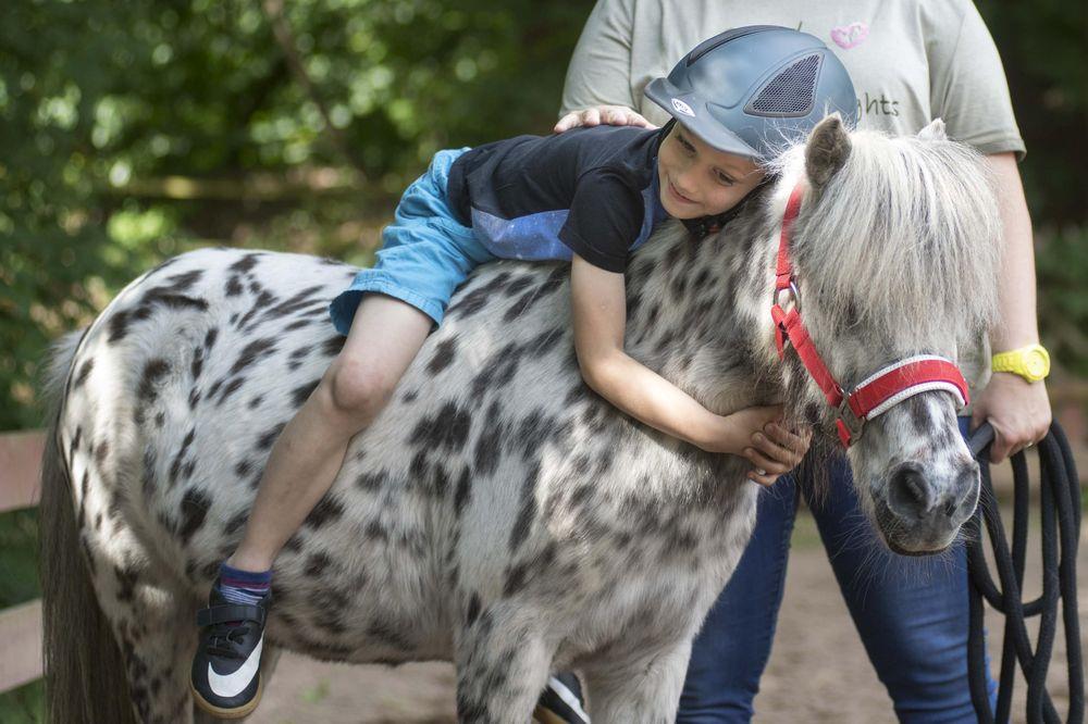 Ein kleiner Junge, der auf einem Pferd liegt und eine Frau, die das Kind festhält