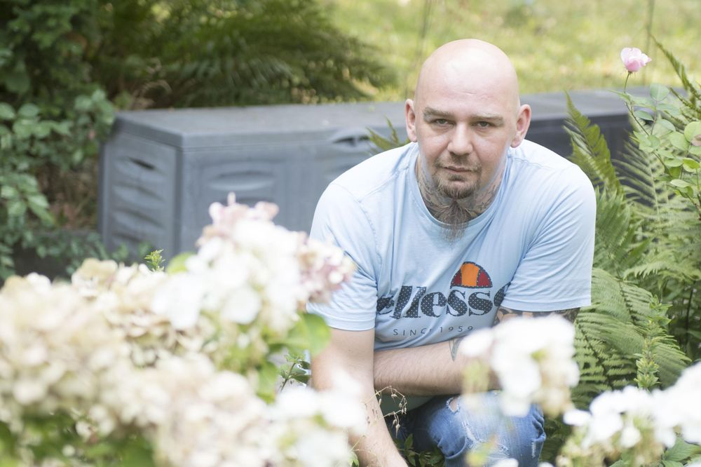 Ein Mann arbeitet im Garten und lächelt in die Kamera.