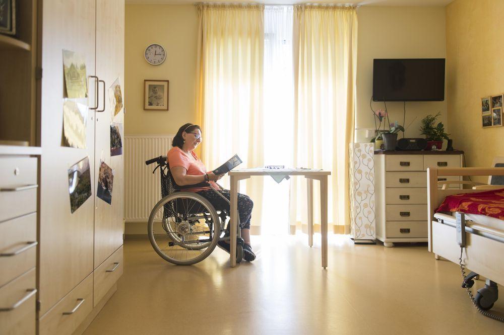 Eine Frau sitzt in ihrem Rollstuhl in ihrem Zimmer und liest Zeitung.