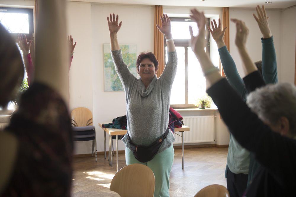 Mehrere Personen machen in einem Stuhlkreis Gymnastik. Sie stehen und halten ihre Arme hoch in die Luft