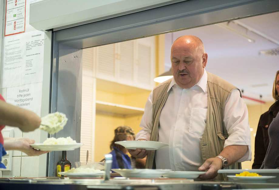 An einer Durchreiche werden Teller mit Kartoffelbrei ausgeteilt. Ein Mann nimmt sich einen Teller.