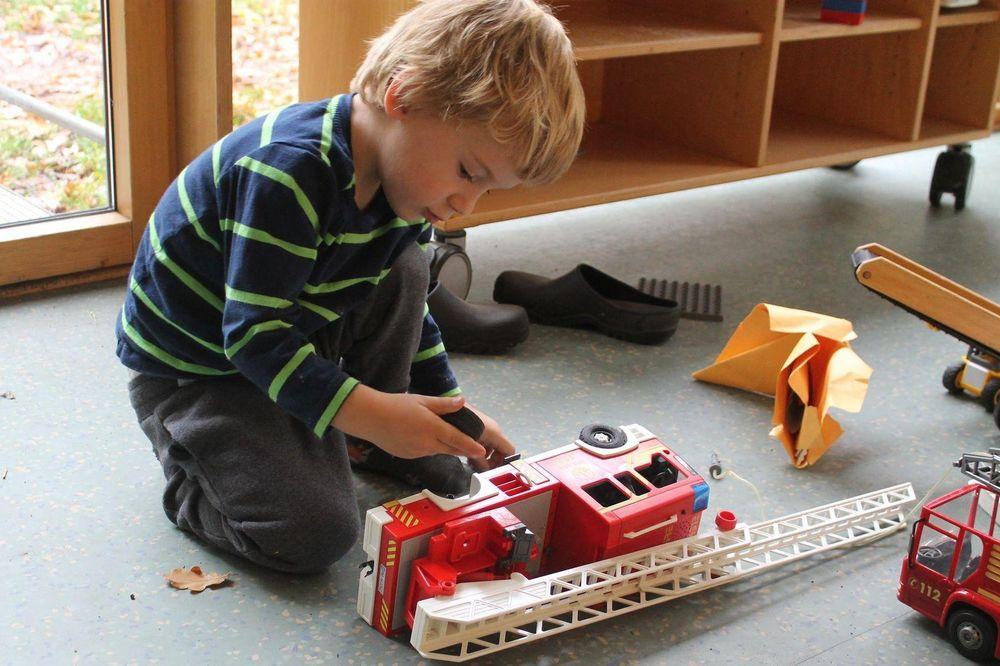 Ein kleiner blonder junge, der mit einem Feuerwehrauto spielt