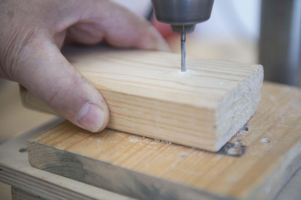 Ein Stück Holz,in das gebohrt und mit einer Hand gehalten wird.