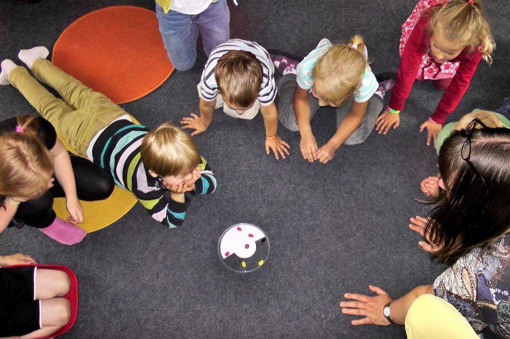 Eine Gruppe von Kinder, die um ein Spiel sitzen