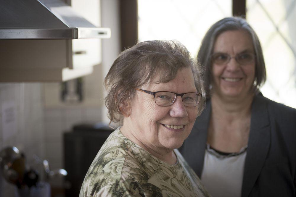 Zwei Frauen stehen in einer Küche und lächeln in die Kamera.