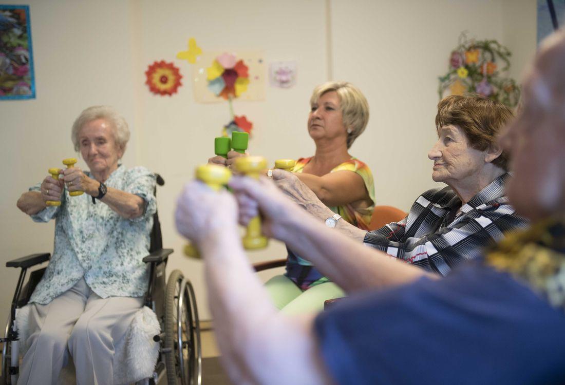 Pflegerin macht mit Senioren im Sitzen Gymnastik