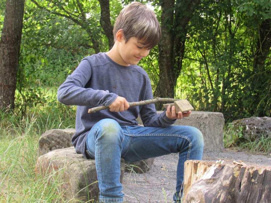 Ein etwa 9-jähriger Junge sitzt auf einem Stein. Mit einem Stein in der Hand schleift er die Rinde eines Stocks ab.