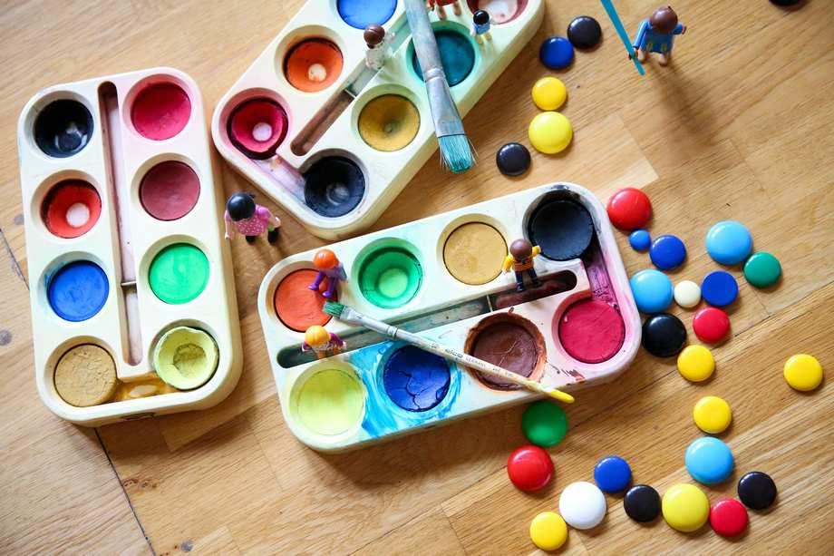 Drei bunte Wasser-Farbkästen stehen auf einem Tisch.