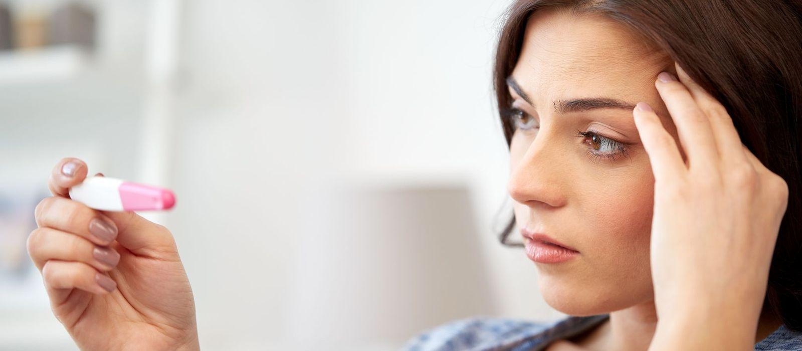 Eine Frau betrachtet einen Schwangerschaftstest, hält sich dabei den Kopf und hat einen kritischen/verzweifelten Blick.