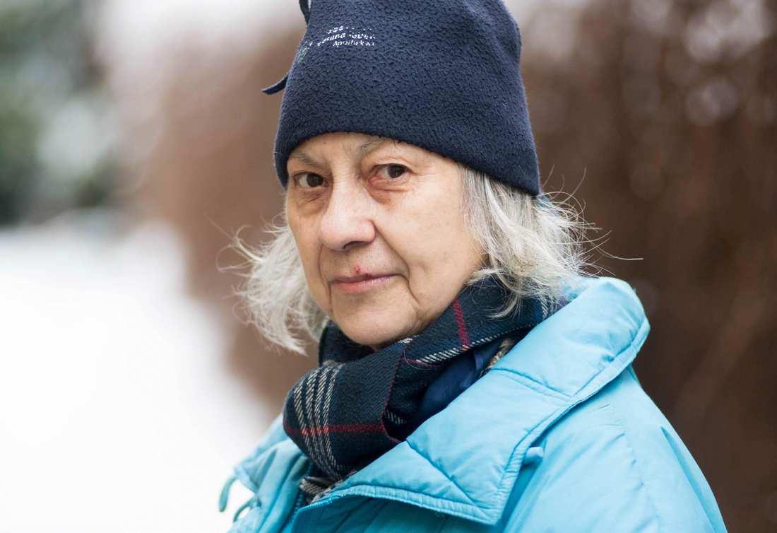Eine ältere Dame mit dunkler Mütze und langen weißen Haaren. Sie trägt einen abgegriffenen Schal und eine alte, hellblaue Steppjacke.
