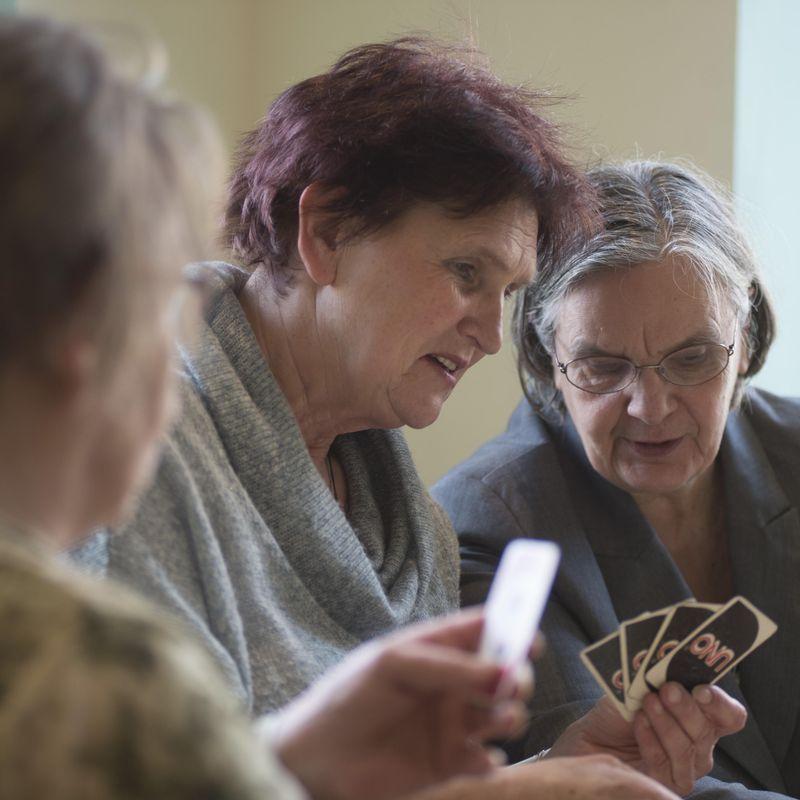 Drei ältere Frauen, die miteinander Karten spielen.