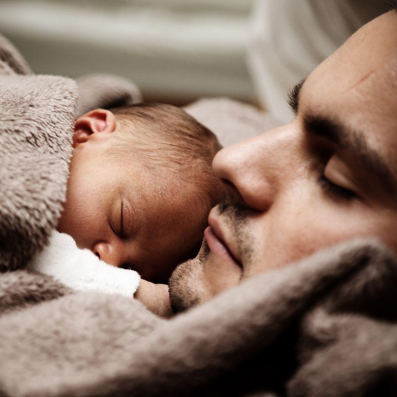 Ein Mann liegt mit einem Baby auf der Brust und mit einer Decke umkuschelt da. Beide haben die Augen geschlossen.