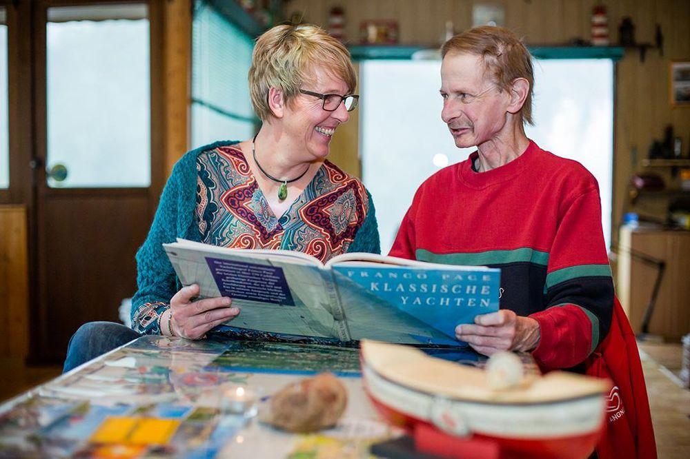 Die Pflegefachkraft liest mit dem zu betreuenden Mann eine Zeitschrift.