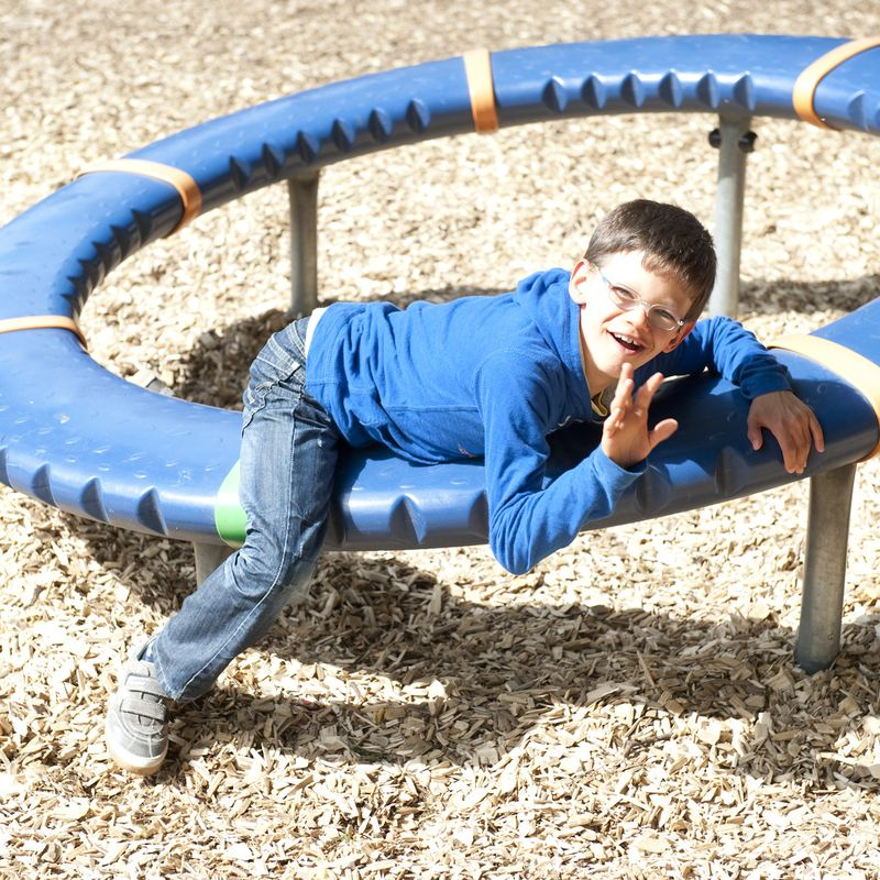 Ein Junge liegt auf einem Spielgerät auf einem Spielplatz.