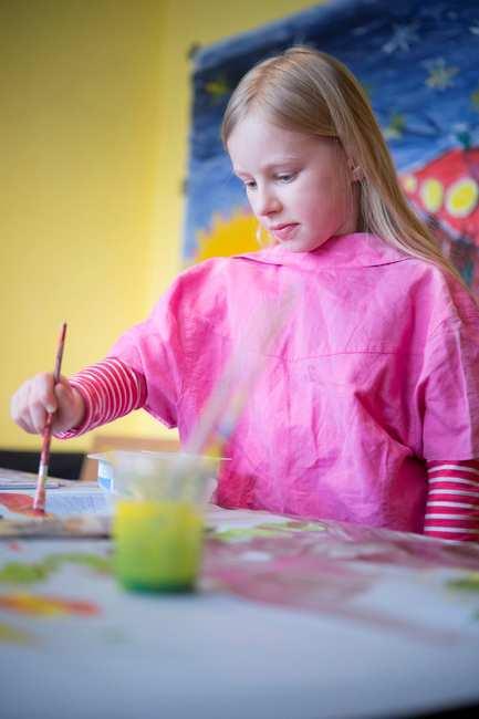Ein blondes junges Mädchen steht mit Pinsel an einem Maltisch.
