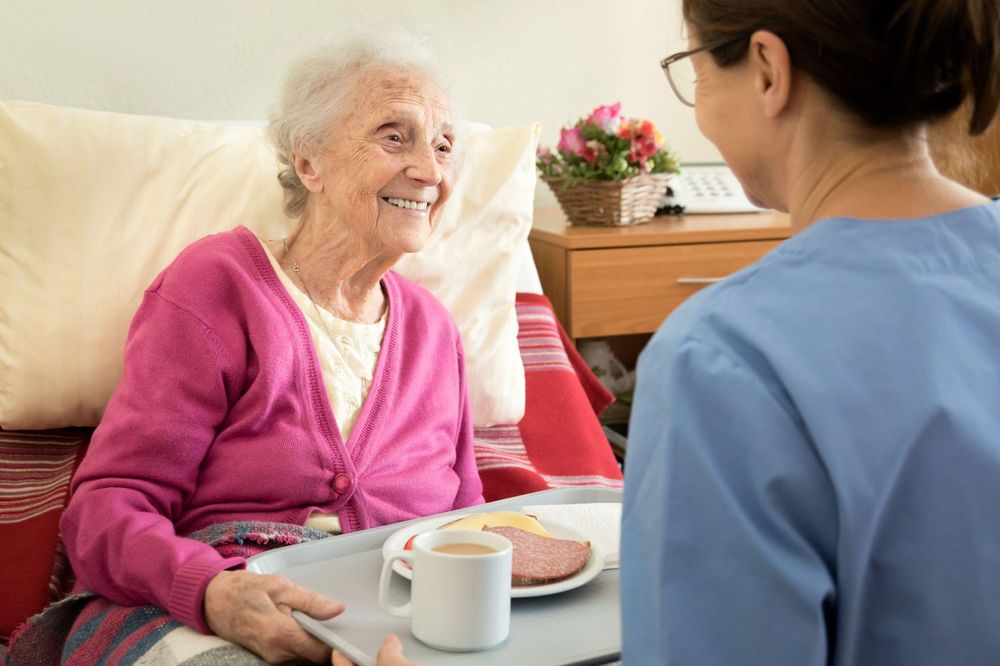Eine Senioren bekommt von einer Pflegerin Essen an ihr Bett gereicht.