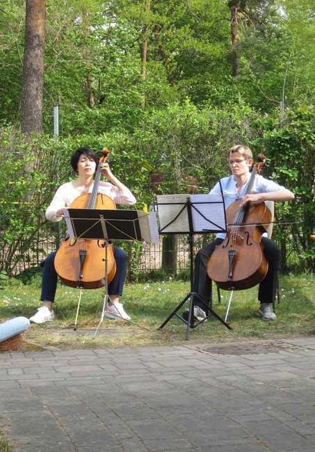 Zwei Frauen sitzen mit Notenständern und Cello vor grüner Hecke. Sie spielen konzentriert ihr Instrument.