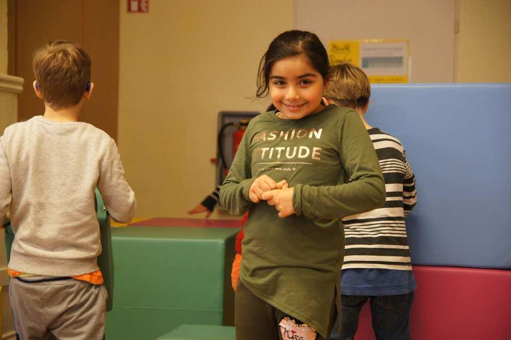 Ein Mädchen mit einem grünen Shirt, das in die Kamera lächelt.