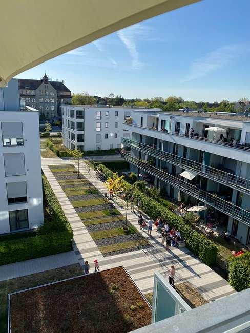 Blick vom 3. Stock auf eine neuere Wohnanlage. Die dreistöckigen Gebäude sind von Balkonen und kleinen Gärten umgeben.