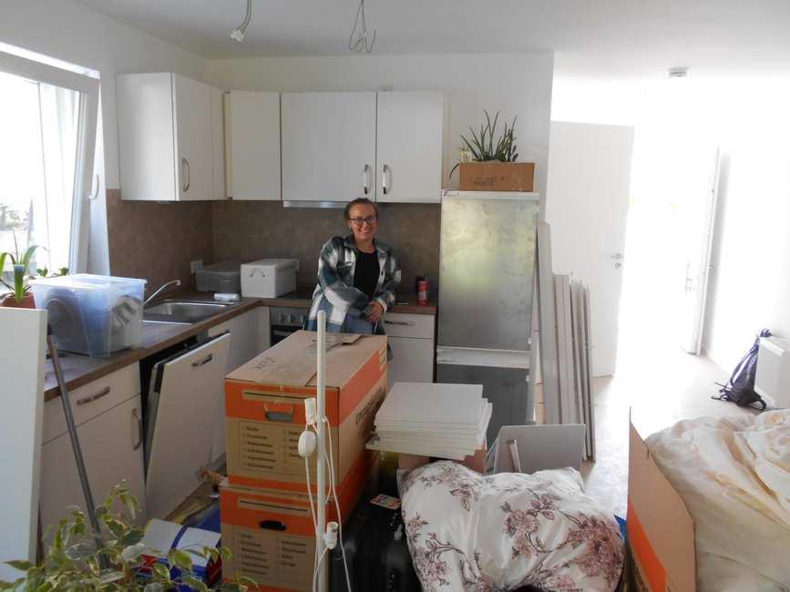 Mieterin Selina, eine Frau Anfang 20, steht lächelnd und umgeben von zahlreichen Umzugskartons in ihrer neuen Küche.