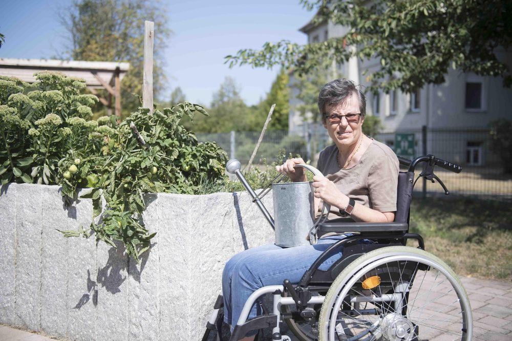 Eine Frau im Rollstuhl steht an einem Tomaten-Hochbeet und hat eine Gießkanne auf dem Schoß.