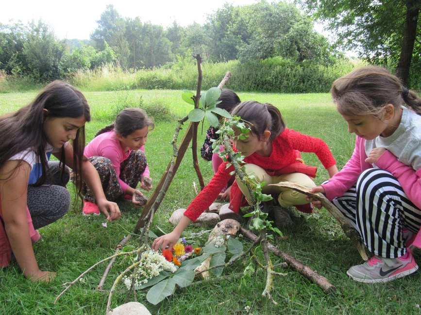 Vier Mädchen bauen auf einer Wiese aus Stöcken, Blättern und Blüten eine kleine Hütte.