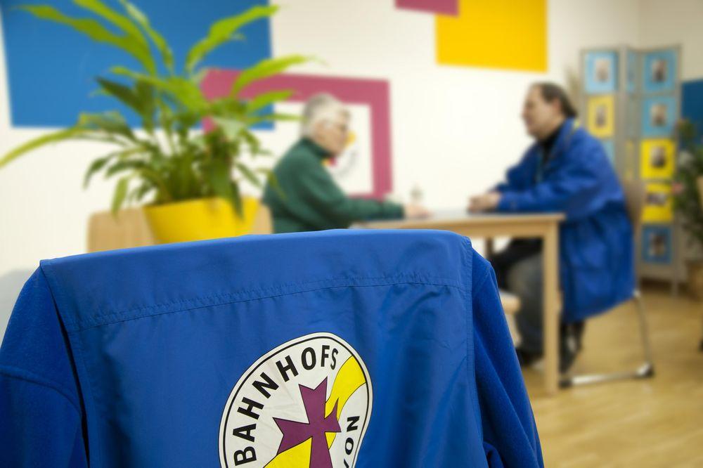 Im Vordergrund hängt eine blaue Bahnhofsmission-Jacke über einem Stuhl. Im Hintergrund ist ein Beratungsgespräch zu sehen.
