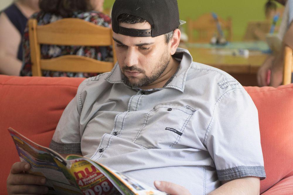 Ein Bewohner sitzt auf einer Couch und liest eine Zeitschrift.