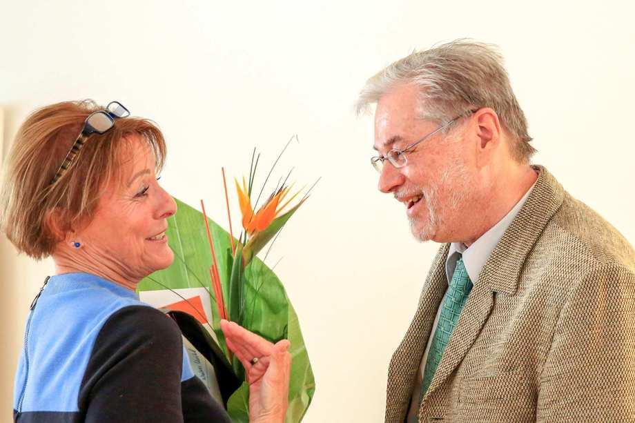 Gabriele Koszanowski überreicht Walter Knöbl einen Blumenstrauß. Beide lachen herzlich.