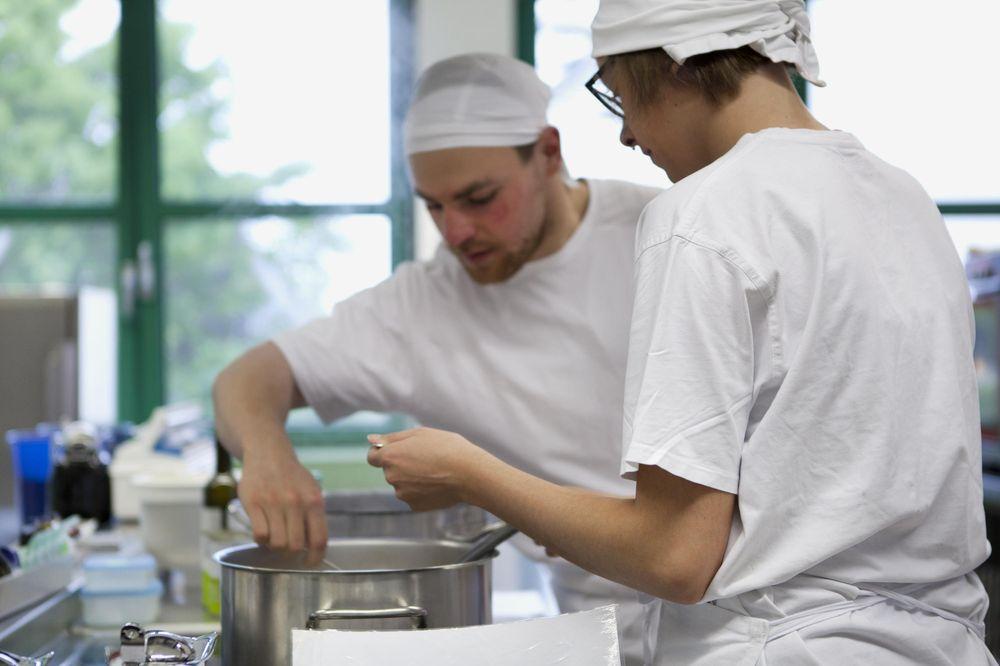 Ein junger Mann und eine junge Frau in weißer Küchenkleidung und Mütze an einem Kochtopf