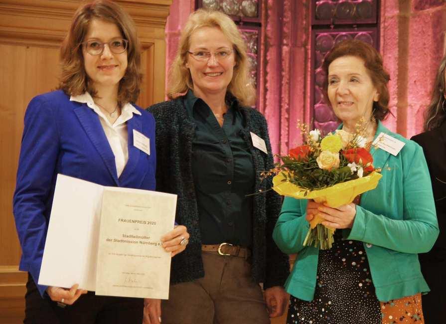 Drei Frauen strahlen in die Kamera. Eine hält eine Urkunde in der Hand, eine andere einen Blumenstrauß
