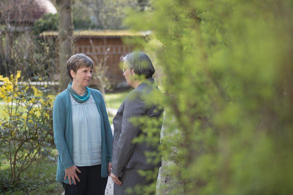 Zwei Frauen stehen im Grünen und lächeln sich an.