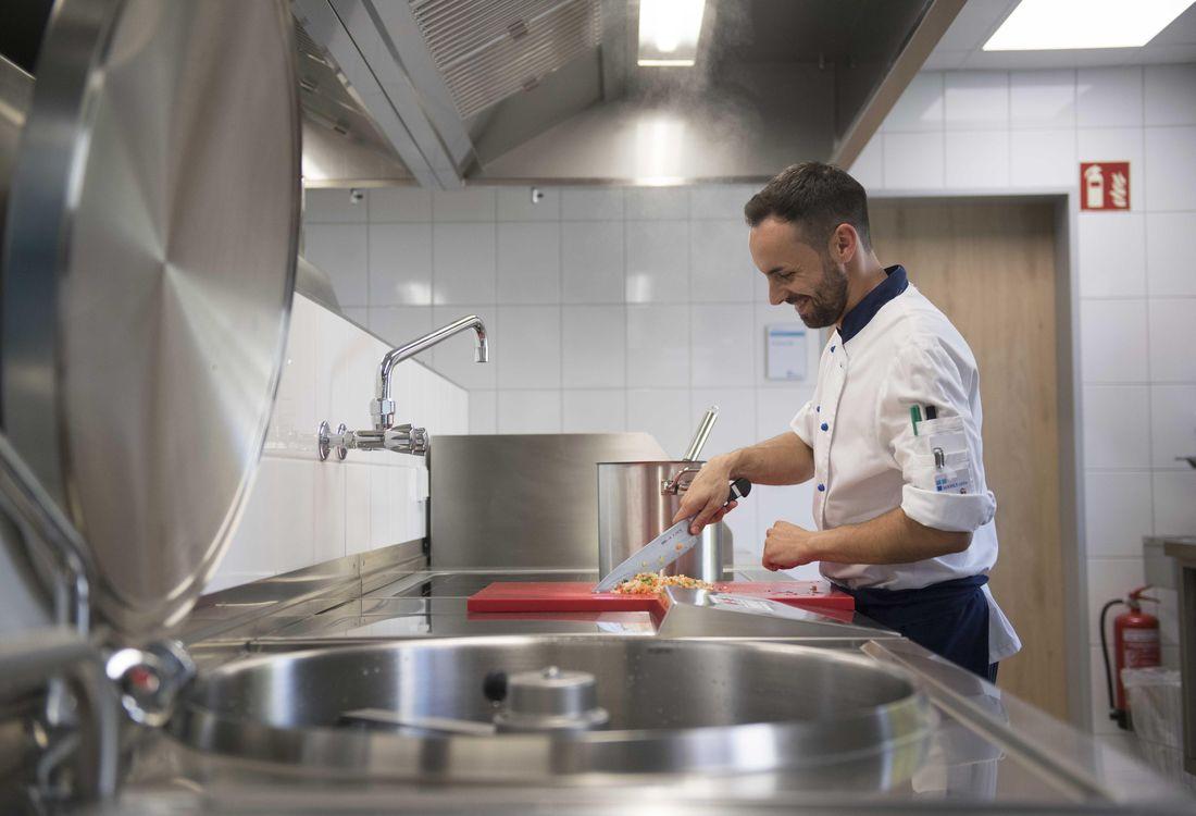 Ein Koch schneidet in der hauseigenen Küche Gemüse.