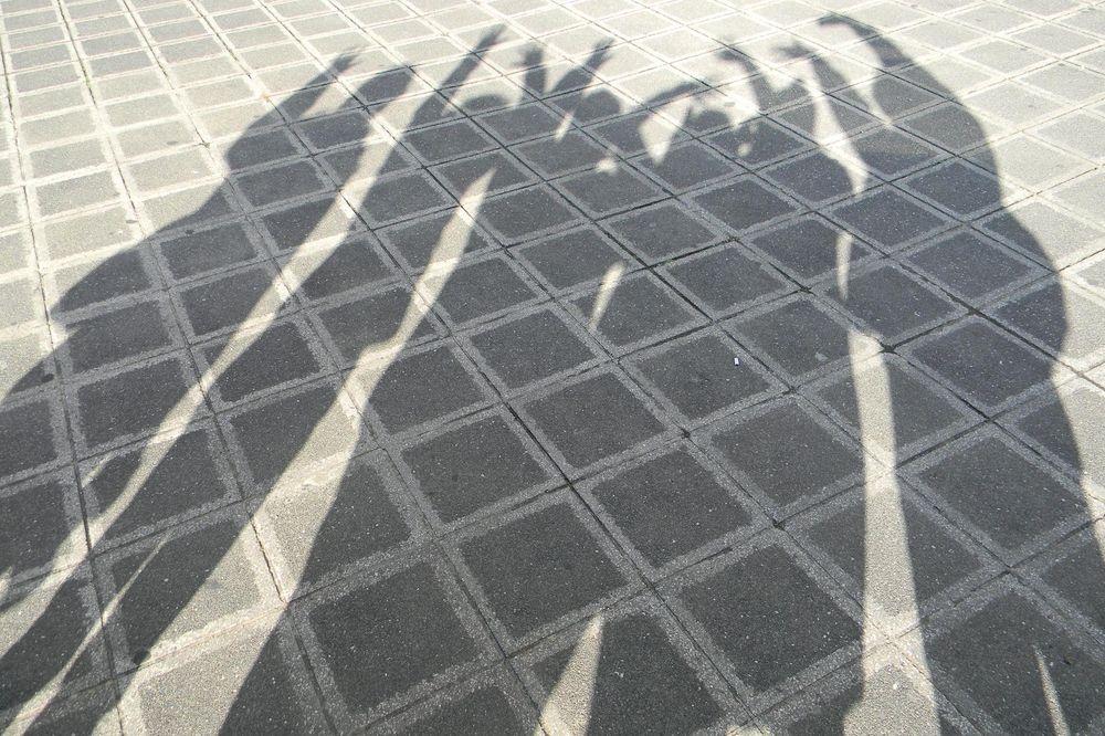 Die Schatten von einer Gruppe von Leuten die ihre Hände in der Luft haben