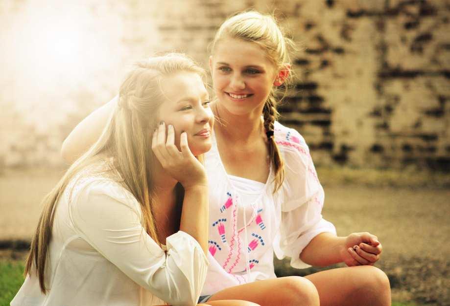 Zwei blonde Teenager-Mädchen sitzen an einer Mauer. Sie lächeln.