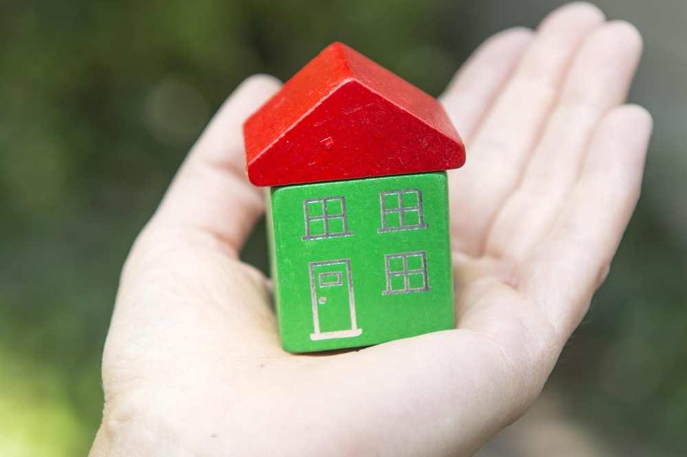 Eine Hand hält ein kleines, grünes Holzhaus mit rotem Dach.