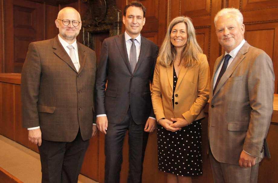 Vier Männer und eine Frau stehen nebeneinander. Sie tragen Anzüge und Blazer.