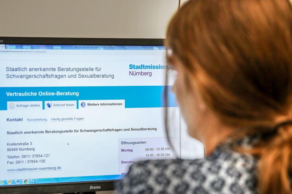 Eine Frau sitzt vor einem Computerbildschirm, auf dem die Startseite der Onlineberatung für Schwangerschafts- und Sexualfragen abgebildet ist.