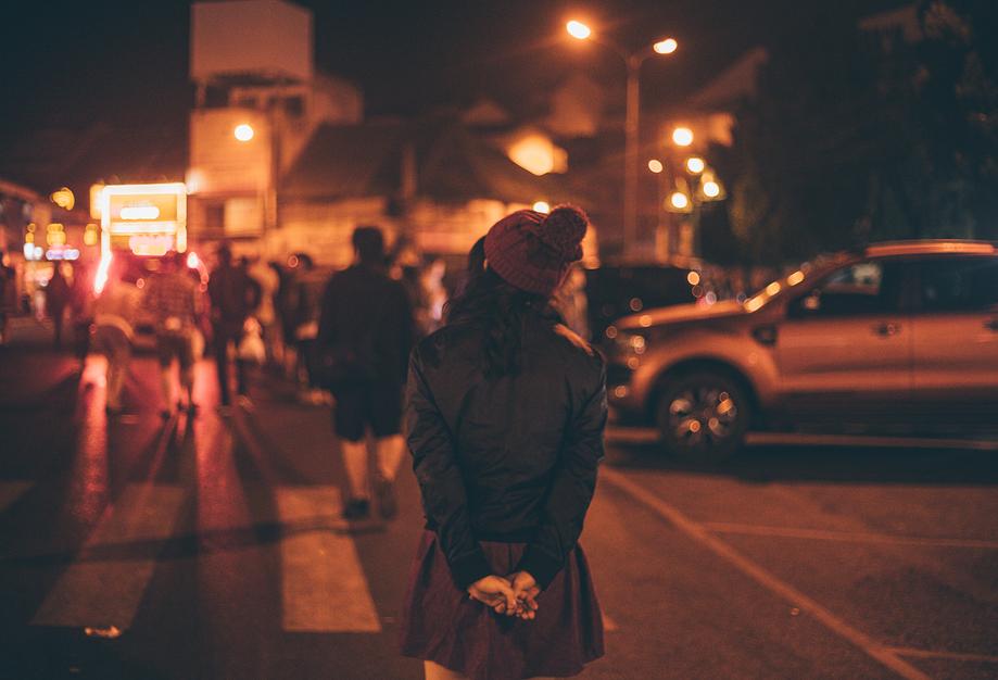Blick auf eine nächtliche Straße: Eine Frau hält die Hände hinter ihrem Rücken zusammen und läuft über eine Straße. Im Hintergrund sind andere Menschen unscharf zu erkennen.