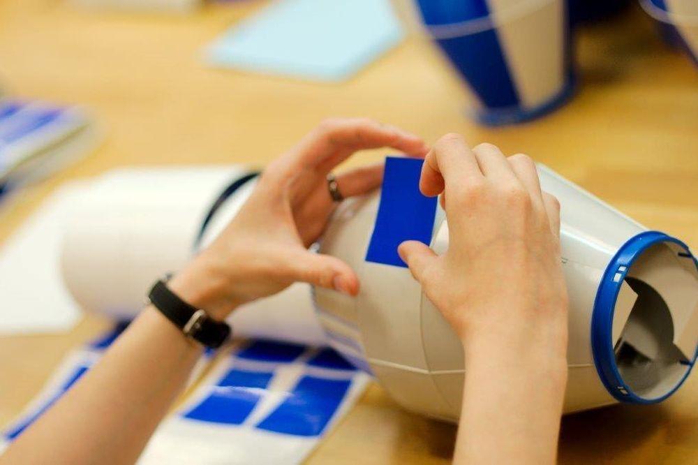 Zwei Hände, die einen weißen Gegenstand mit blauen Rechtecken bekleben