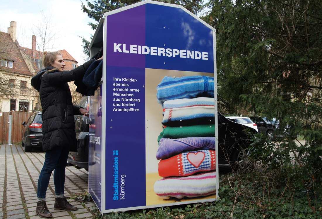 Eine Frau wirft etwas in einen Kleidercontainer.