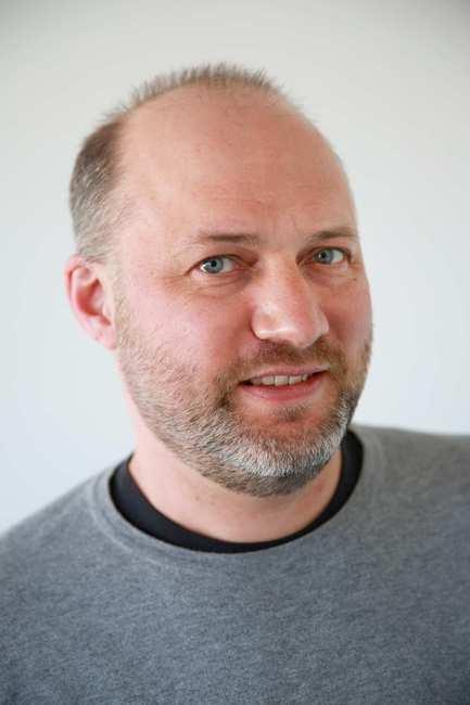 Ein Mann mit Drei-Tage-Bart. Er trägt einen grauen Pullover.