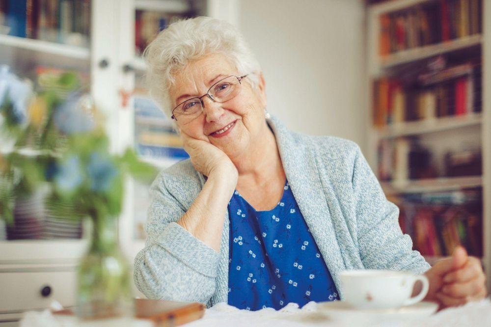 Portrait einer älteren Dame, die an einem gedeckten Kaffee-Tisch sitzt