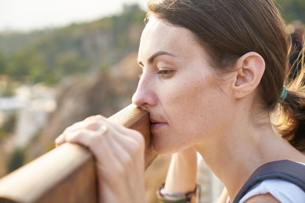 Eine Frau schaut nachdenklich über ein Geländer.