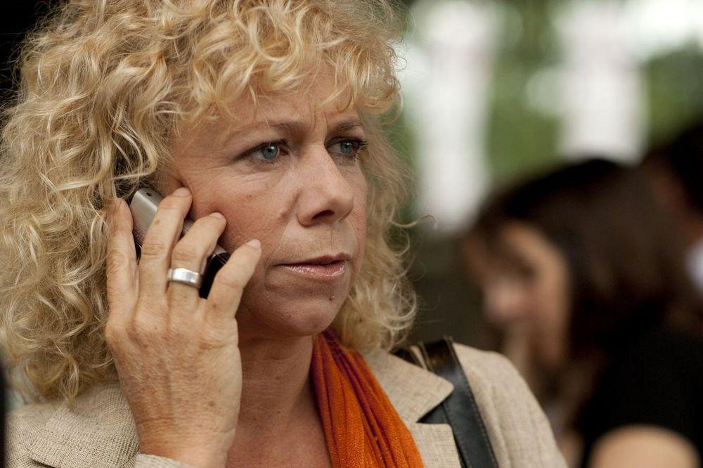 Eine blonde Frau hält ein Telefon an ihr Ohr und schaut nachdenklich.