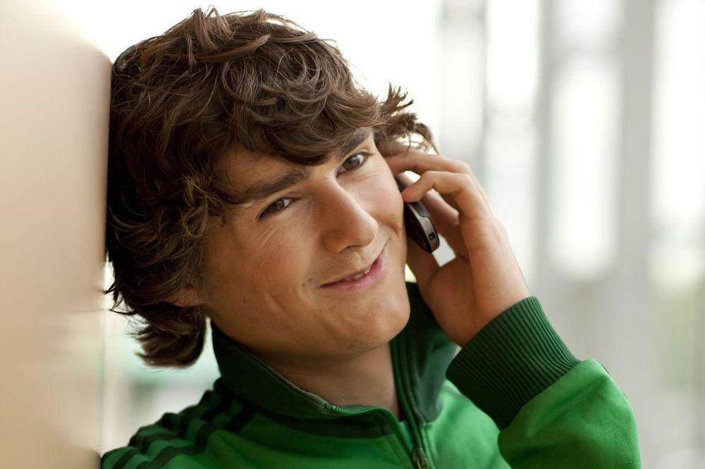 Ein junger Mann lehnt lächelnd an einer Wand und telefoniert.