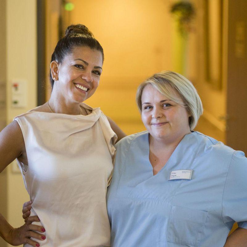 Zwei Frauen, eine Pflegedienstleitung und eine Pflegefachkraft, stehen nebeneinander und lächeln