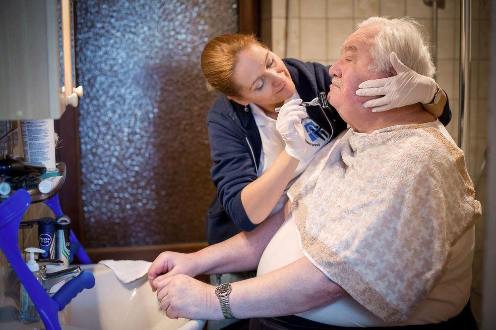 Die Pflegefachkraft rasiert den Bart des Seniors in seinem Badezimmer.