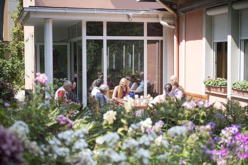 Eine Gruppe sitzt im sonnigen Garten vor einem Haus und unterhält sich.